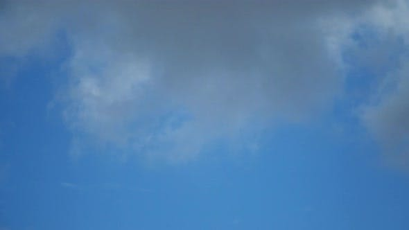 The movement of white clouds against the blue sky. Time lapse