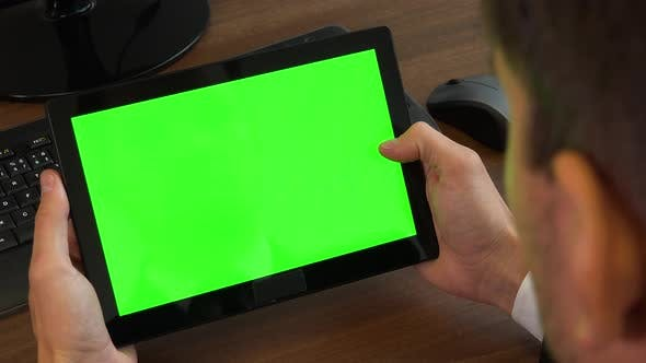 Thumbnail for An office worker scrolls at a tablet with a green screen at a desk with a computer - closeup