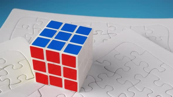 Rubik cube at the top of white jigsaw puzzle.