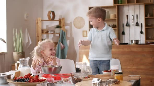 Messy Kids Playing with Flour while Making Batter