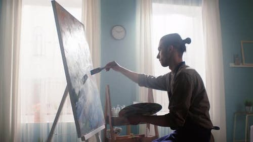 Inspired Young Man Is Painting on Canvas