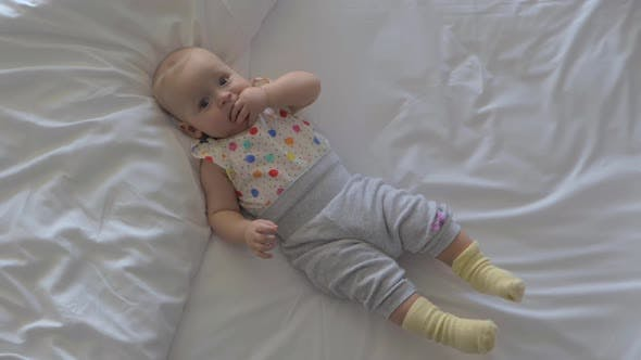 Quiet Baby Girl on the Bed at Home
