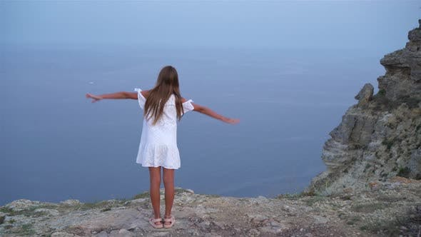 Thumbnail for Little Girl on Top of a Mountain Enjoying Valley View Before Sunset