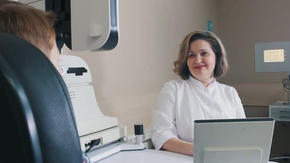 Ophthalmologist Treatment -a Smiling Woman Doctor Checking Boy's Vision