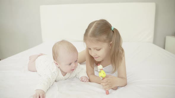 Thumbnail for Little Baby Infant Newborn And His Older Sister Lie On A White Sheet On The Bed