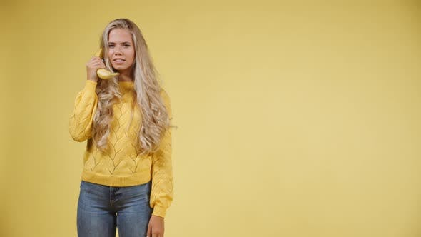 A model with Long Blonde Hair Talking on a Banana Phone and then Acting Shocked