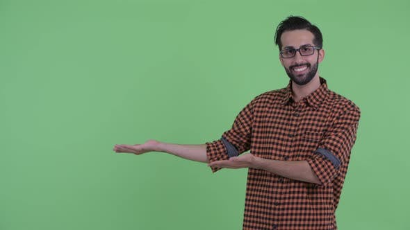 Thumbnail for Happy Young Bearded Persian Hipster Man Talking While Showing Something
