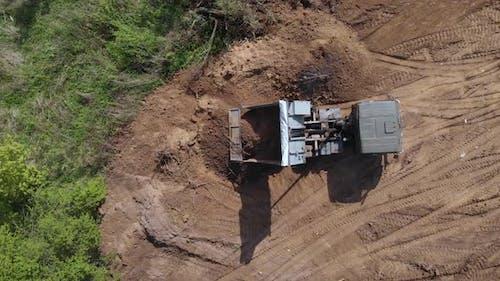 Top aerial view of tipper unloading ground on further construction site