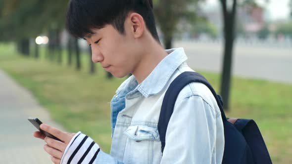 Thumbnail for Asian Teenage Boy Typing on Smartphone Outdoors
