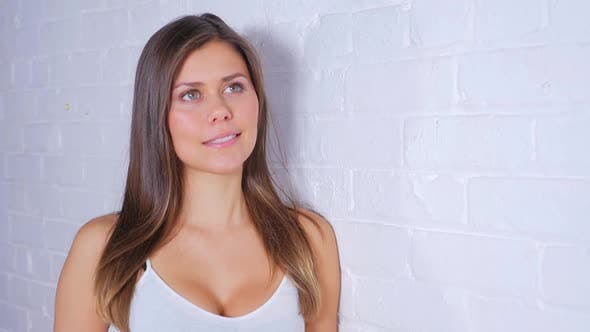 Thumbnail for Young Attractive Female Doing Different Poses While Smiling And Leaning Against A White Brick Wall 3