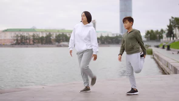 Thumbnail for Asian Mother and Son Doing Stretching Exercise on Urban Riverside Sidewalk