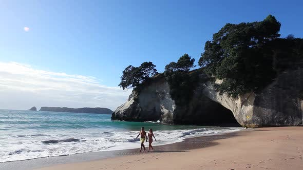 Thumbnail for Couple walking along beach, Te Whanganui-A-Hei (Cathedral Cove), New Zealand