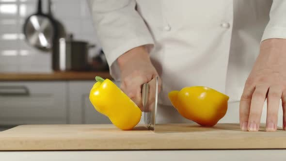 Thumbnail for Chef Chopping A Yellow Bell Pepper On Wooden Board