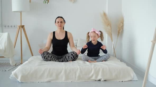 Mother with Daughter Meditating in Lotus Pose