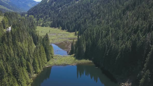 Thumbnail for Aerial Drone Footage Of A Lake And Valley With Reflections Of Evergreen Trees On A Mountain 1