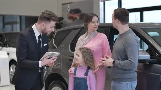Thumbnail for Confident Caucasian Car Dealer Presenting New Automobile To Young Family. Trader with Tablet Talking