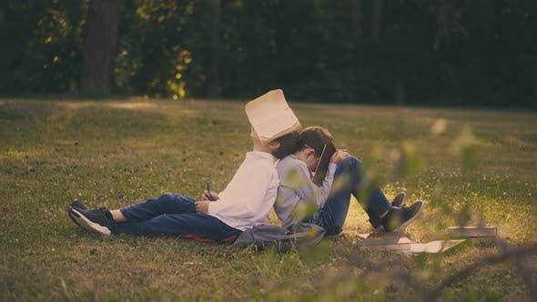 Little Schoolboys Hide Faces Behind Books in Sunny Garden