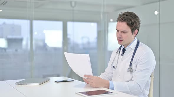 Thumbnail for Hardworking Young Doctor Reading Documents in Office