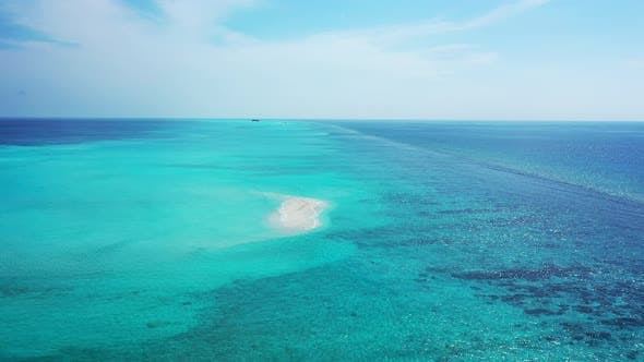 Wide fly over clean view of a sunshine white sandy paradise beach and blue sea background in best