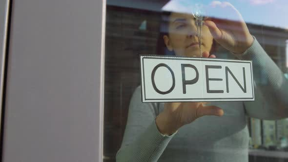 Thumbnail for Woman Hanging Banner with Closed Word on Door