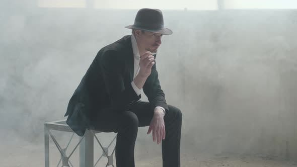 Thumbnail for Portrait Handsome Confident Man in a Hat Throws Up and Catches the Coin Sitting in an Abandoned