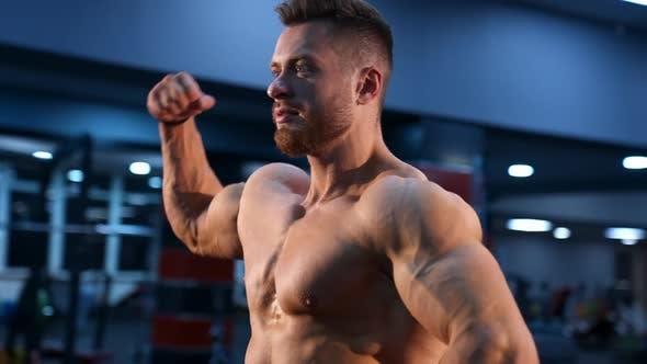 Circle View auf Bodybuilder ohne Shirt im Fitnessstudio. Mann mit starken Händen und großen Muskeln.
