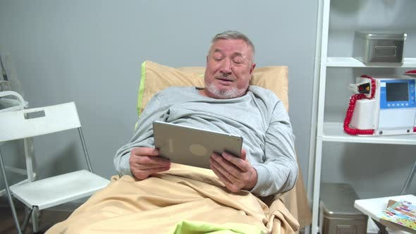 Thumbnail for Man Lie on Bed and Talk with Someone on the Tablet and Wave His Hand
