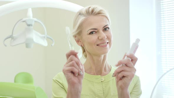 Smiling Stomatologist Showing Toothpaste and Toothbrush
