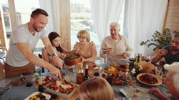 Thumbnail for Man Cutting Roasted Turkey for Family at Thanksgiving Dinner