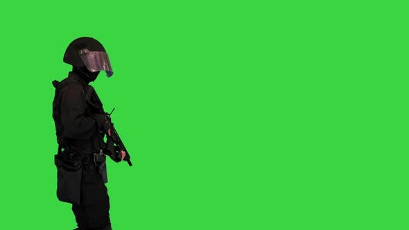 Swat Police Operator with Assault Rifle Walking By on a Green Screen Chroma Key