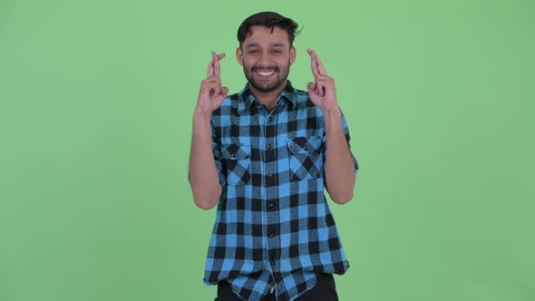 Thumbnail for Happy Young Bearded Persian Hipster Man Wishing with Fingers Crossed