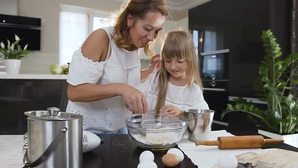 Little Girl Helping her Mom in the Kitchen by Stirring the Ingredients
