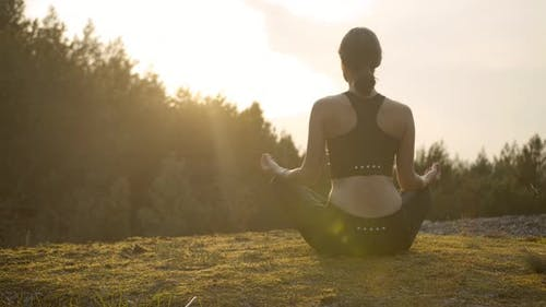 Young Woman Meditating on Sunset Background