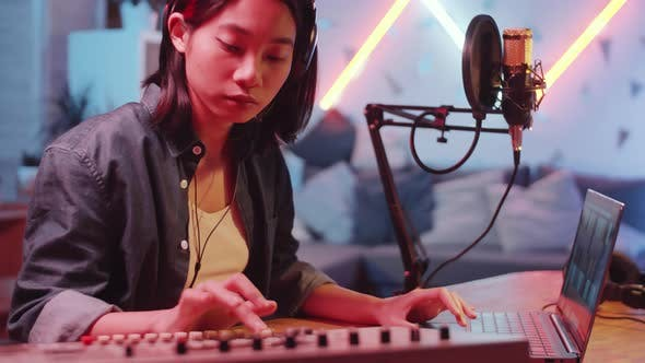 Asian Female Musician Using Sound Mixer and Laptop in Home Recording Studio