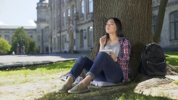 Thumbnail for Exchange Student Sitting Under Tree, Holding Notebook, Thinking, Check-In List