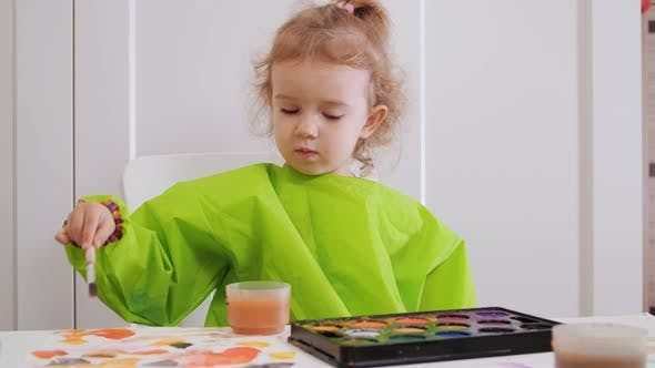 Cute Toddler Girl Painting with Gouache and Watercolor Paints at Home