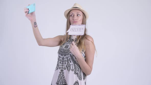 Cover Image for Portrait of Happy Blonde Tourist Woman Taking Selfie with Paper Sign