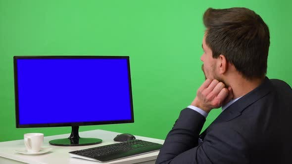 Thumbnail for A Young Businessman Sits at a Desk and Looks at a Desktop Computer, Bored - Green Screen Studio