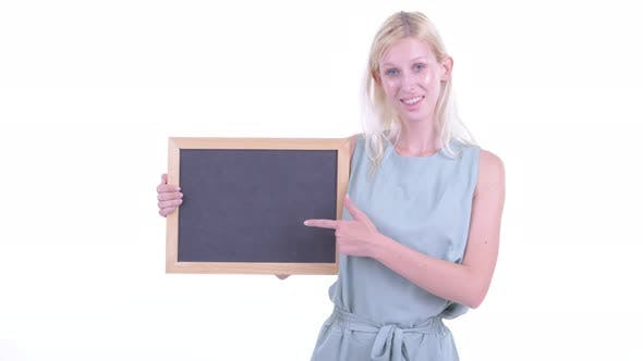Thumbnail for Happy Young Blonde Woman Holding Blackboard and Giving Thumbs Up