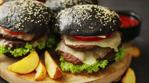 Black Double Burgers with Cheese. Cheeseburgers From Japan with Black Bun on Dark Background