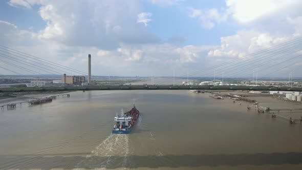 Large Ship Travelling Under Suspension Bridge