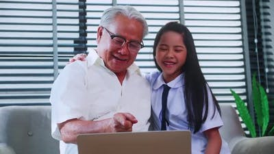 An Asian grandfather and granddaughter spending time together in the living room.
