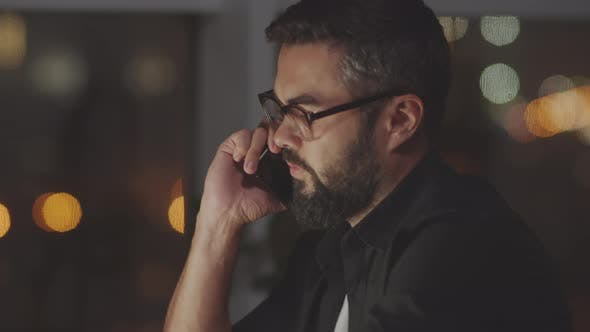 Thumbnail for Businessman Talking on Phone in Dark Office