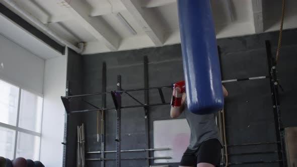 Weibliche Boxer Schlagen mit schwerer Tasche im Fitnessstudio
