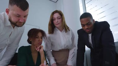Team of Managers Bending Over Table to Discuss Plan