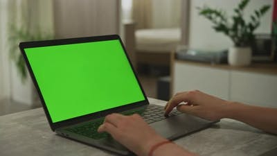 Hands Typing on a Laptop with Chroma Key Green Screen Indoors