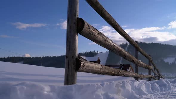 Thumbnail for Winter Rural Scene with Old Abandoned Wooden Fence and Snowy Wooden House and Mountains