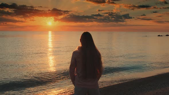 Thumbnail for Woman with Outstretched Arms Enjoying the Beauty of Sunset on the Sea