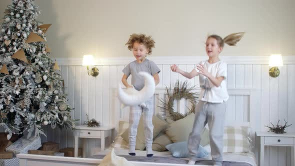 Thumbnail for Kids Laughing and Jumping on Bed in Room Decorated for Christmas
