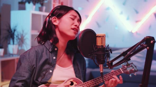 Asian Female Musician Playing Guitar and Recording Song at Home